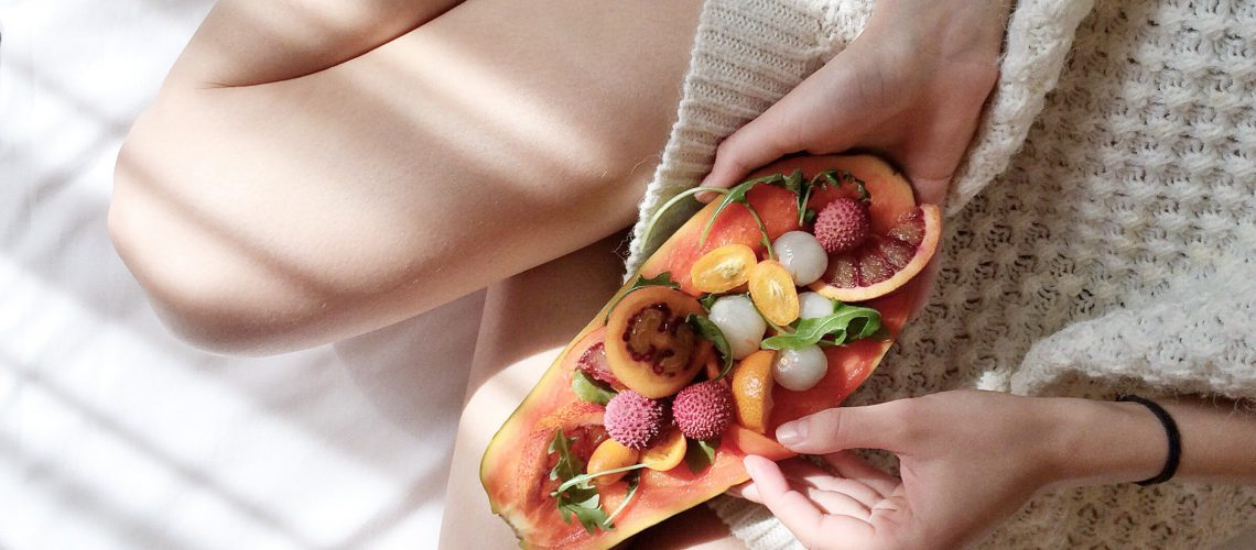 person-holding-papaya-fruit-on-bed-1030870